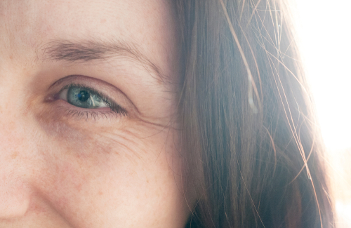 smiling woman with no make up blue eyes brown hair and freckles.showing crows feet around the eyes-img-blog