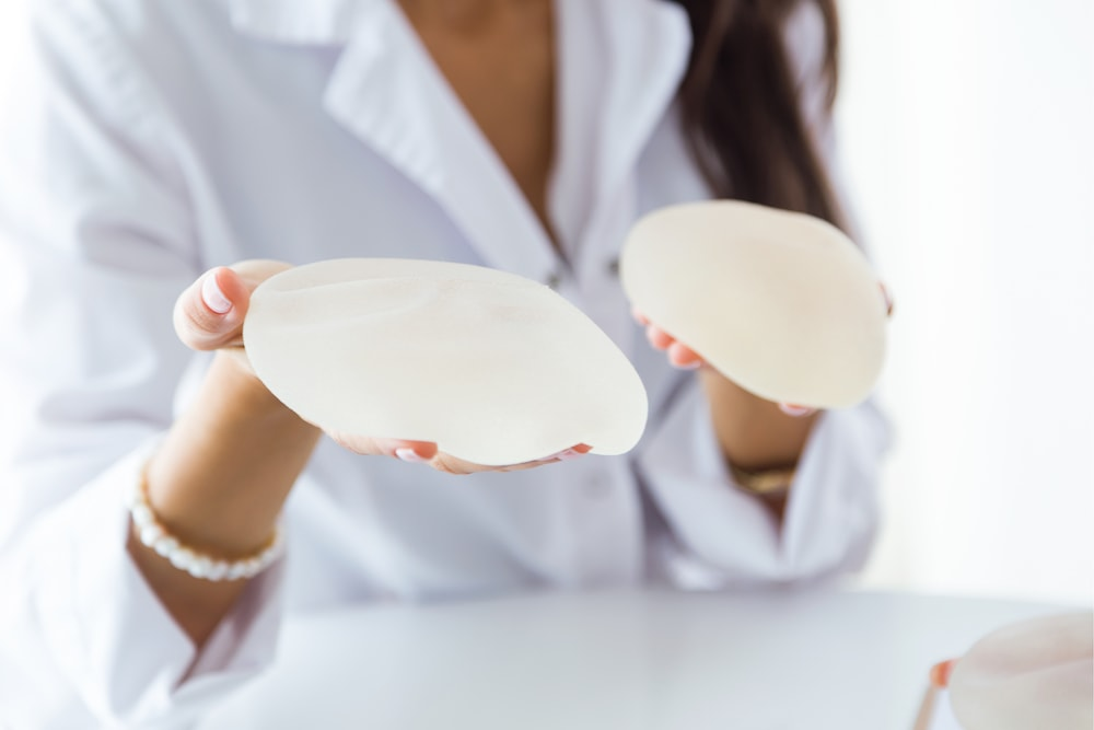 Close-up of plastic surgeon holding out two different breast implant options.